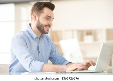 Young smiling broker in blue shirt typing on laptop keypad and looking at display while analyzing online data