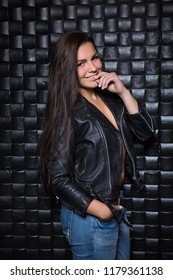 Young smiling brunette in black jacket posing near the wall
