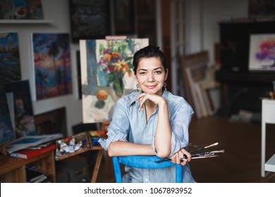 A young smiling brunette woman artist in her Studio is holding a brush. Near her easel, paintings and various art equipment.
