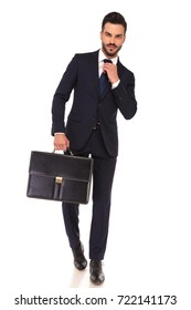 young smiling business man holding briefcase is fixing his tie and walks on white background