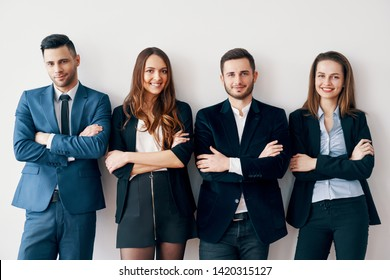 Young smiling business people with arms crossed lean to wall in office. Success teamwork concept