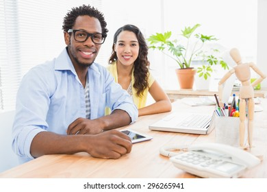Young smiling business people looking at the camera in the office