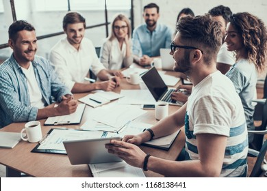 Young Smiling Business People on Meeting in Office. Man showing Project on Tablet to Group of Young Happy Collegues Sitting Together at Table Working on Laptops in Modern Office. Teamwork Concept