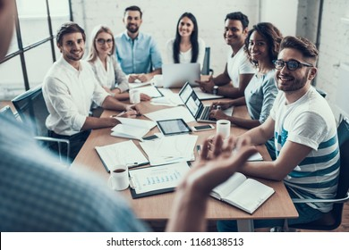 Young Smiling Business People on Meeting in Office. Group of Young Coworkers Sitting Together at Table in Modern Office and Listening to Businessman Presenting. Teamwork Concept. Corporate Lifestyle