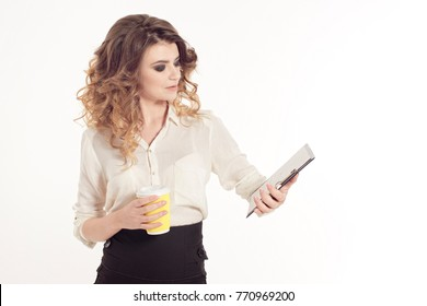 Young smiling business woman with brown curly hair, looking at folder with cup of coffee, isolated on white background.