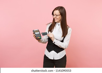 Young smiling business woman holding wireless modern bank payment terminal to process and acquire credit card payments, black card isolated on pink background. Lady boss. Achievement career wealth