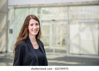 Young smiling business woman - portrait on building glass background