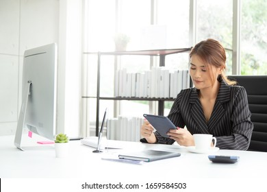 Young smiling business woman sitting at table using smartphone trading online, checking stock market and email. Student learning online.