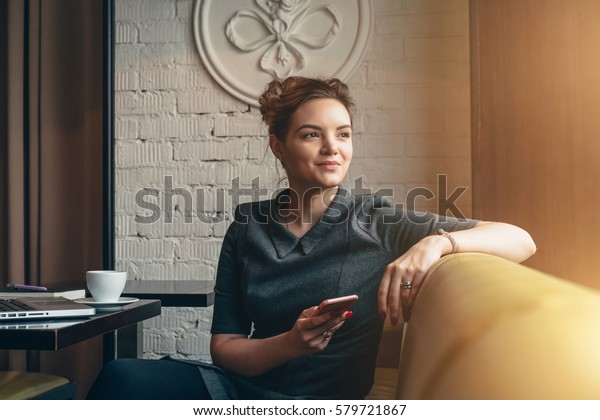 Young smiling business woman sitting in cafe at table, leaning his hand back in chair,looking out window and holding smartphone.On table is laptop, notebook and cup of coffee. Girl using gadget.