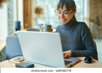 Young smiling business woman in spectacles working on portable laptop computer. Female copywriter sitting at desk and typing on keyboard, working on project, writing down ideas into netbook
