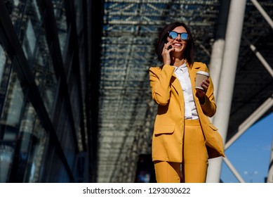 Young smiling business woman in sunglasses and yellow suit stands near office centre with cup of coffee and talks on smart phone. Lunch break among working day. Business lifestyle and success concept.