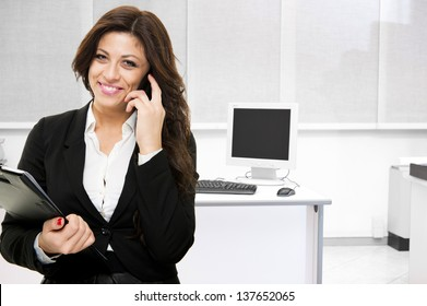 Young smiling business woman talking at the phone on office background