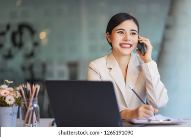 Young smiling business woman using smartphone near computer in office