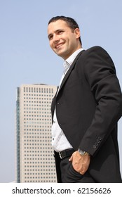 Young smiling businessman in a black suit with modern office building on a background