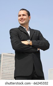 Young smiling businessman in a black suit with sky and modern office building on a background