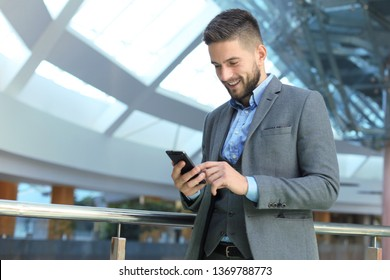 Young smiling businessman calling on phone at office.