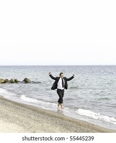 young smiling businessman celebrating on beach