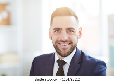 Young smiling businessman in formalwear standing in front of camera inside office during working day