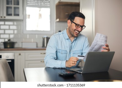 Young smiling businessman hold credit card and holding a piece of paper while sitting in front of laptop.
