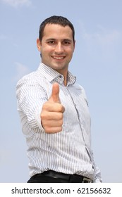 Young smiling businessman showing ok with focus on a face at blue sky background