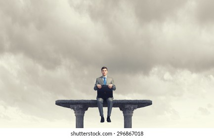 Young smiling businessman sitting on top with briefcase in hands