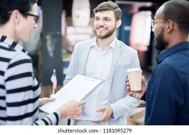 Young smiling businessman standing and discussing report with his colleagues before business conference