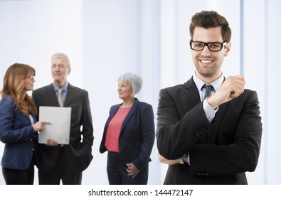 Young smiling businessman standing in office with colleagues in the background