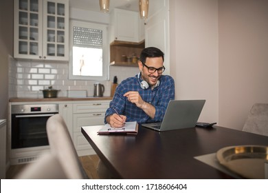 Young smiling businessman working from home writing notes in notebook while using his laptop and wearing headphones around his neck.