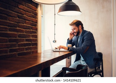 Young smiling businessman working with laptop in city cafe. Drinking coffee and talking on the phone. Wearing suit and stubble