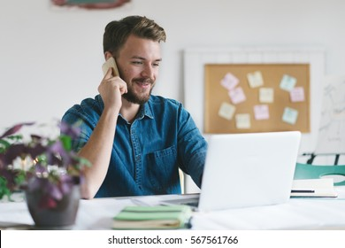 Young smiling businessmen working in his office and  speaking on his mobile phone.