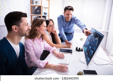 Young Smiling Businesspeople Showing Stock Market Broker Analyzing Graph On Computer At Workplace