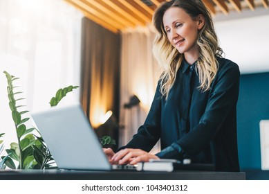 Young smiling businesswoman in black blouse is standing indoor, working on computer. Girl freelancer, entrepreneur works at home. Online marketing, education, e-learning, distance work. Social media.