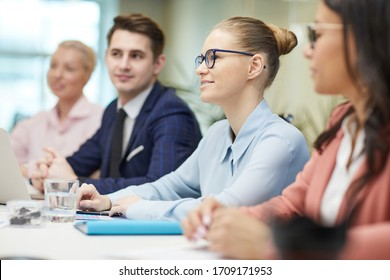 Young smiling businesswoman in eyeglasses sitting at the table and talking to her colleagues during business meeting at office