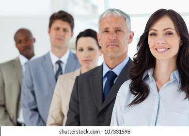 Young smiling businesswoman followed by her full team