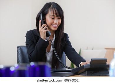 Young smiling businesswoman having conversation on landline phone
