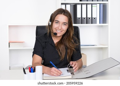 A young smiling businesswoman with headset is writing into a file while sitting at the desk in the office. A shelf is standing in the background. The Woman is looking to the camera.