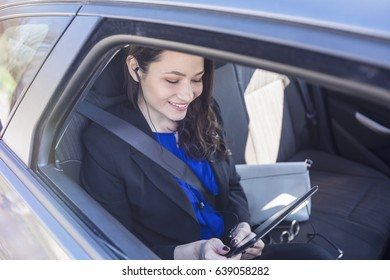 Young smiling businesswoman listening to music in a car