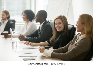 Young smiling businesswoman looking at camera at corporate group meeting, business training participant sitting at conference table with diverse colleagues, company manager portrait at team briefing