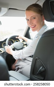 Young smiling businesswoman looking at camera in her car