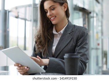 Young smiling businesswoman in office working on digital tablet.