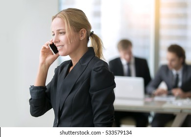 Young smiling businesswoman on phone, colleagues working on the background, daily femme business, can express in several languages, phone etiquette to improve customer service, calling to tech support