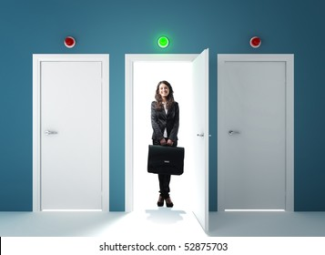 young smiling businesswoman standing infront of the right door
