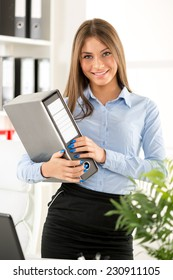 Young smiling businesswoman standing in office in front of shelves with binders, holding a binder.