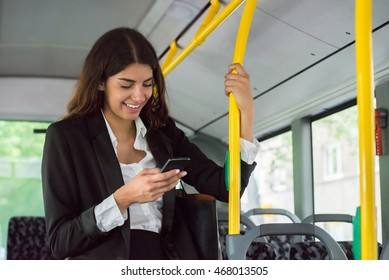 Young Smiling Businesswoman Using Smartphone While Traveling By Public Transport