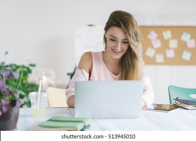 Young smiling businesswoman working in her office and typing on her laptop.
