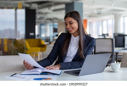 Young smiling businesswoman working at the laptop and reading documents in open space office.