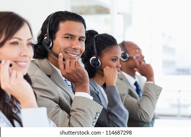 Young smiling call centre employee working among his team