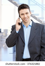 Young smiling caucasian businessman with mobile phone in hand at business office. Suit no tie, standing, looking at camera.