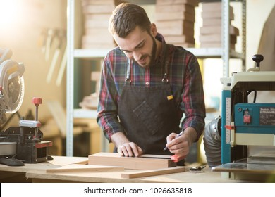 young smiling Caucasian carpenter measuring on a wooden bar standing at a table in a workshop