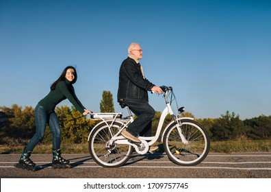 Young smiling caucasian girl on roller skates and a man on a electric bike fun ride together. Active leisure and hobbies. Father and daughter.